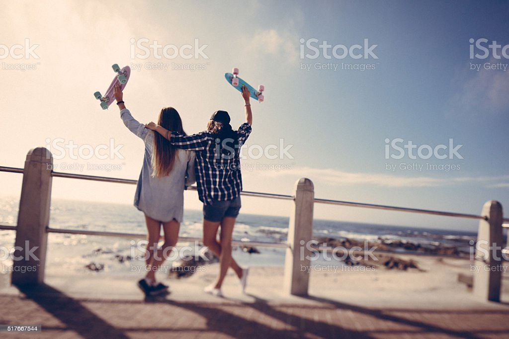 Hipster girls with skateboards on summer day at the beach stock photo