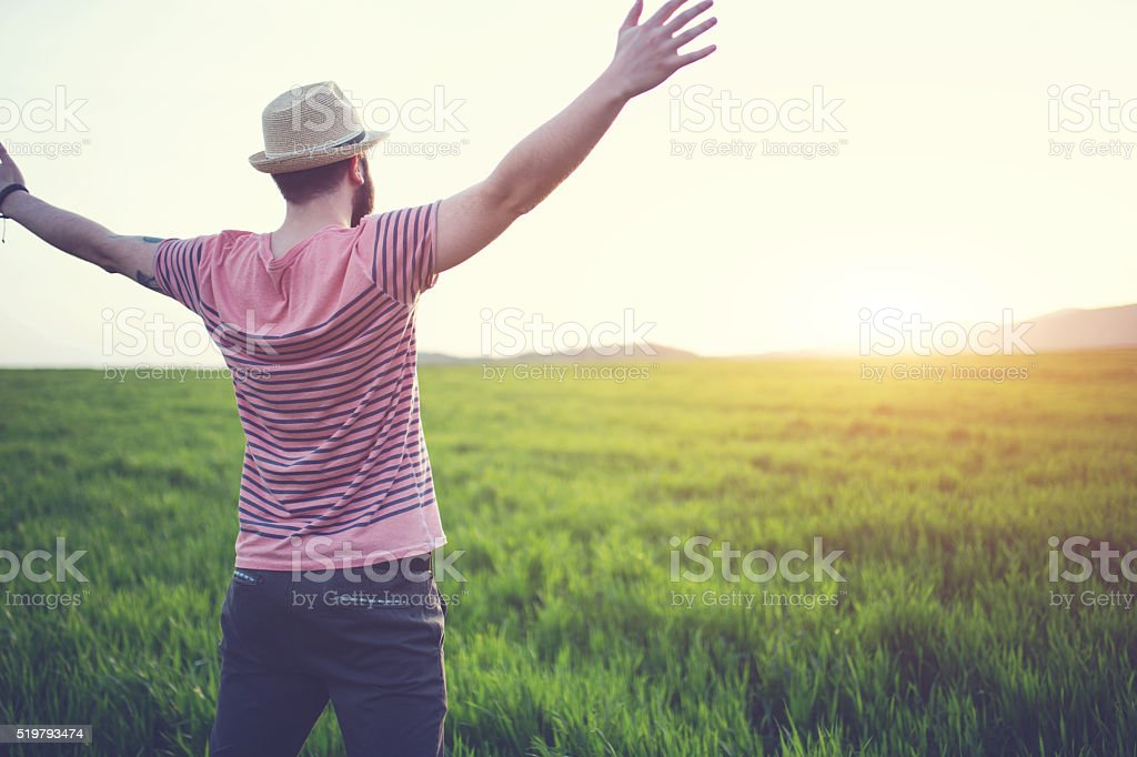 Hipster guy on a green field stock photo