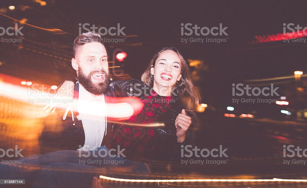 Hipster guy picks his girlfriend up at night in city stock photo