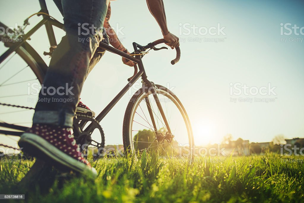 Hipster  guy riding his bicycle on the grass stock photo