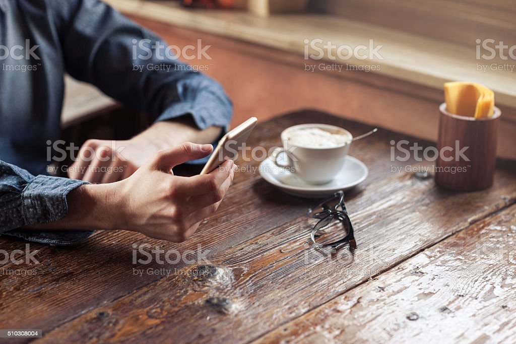 Hipster guy texting with his mobile phone stock photo