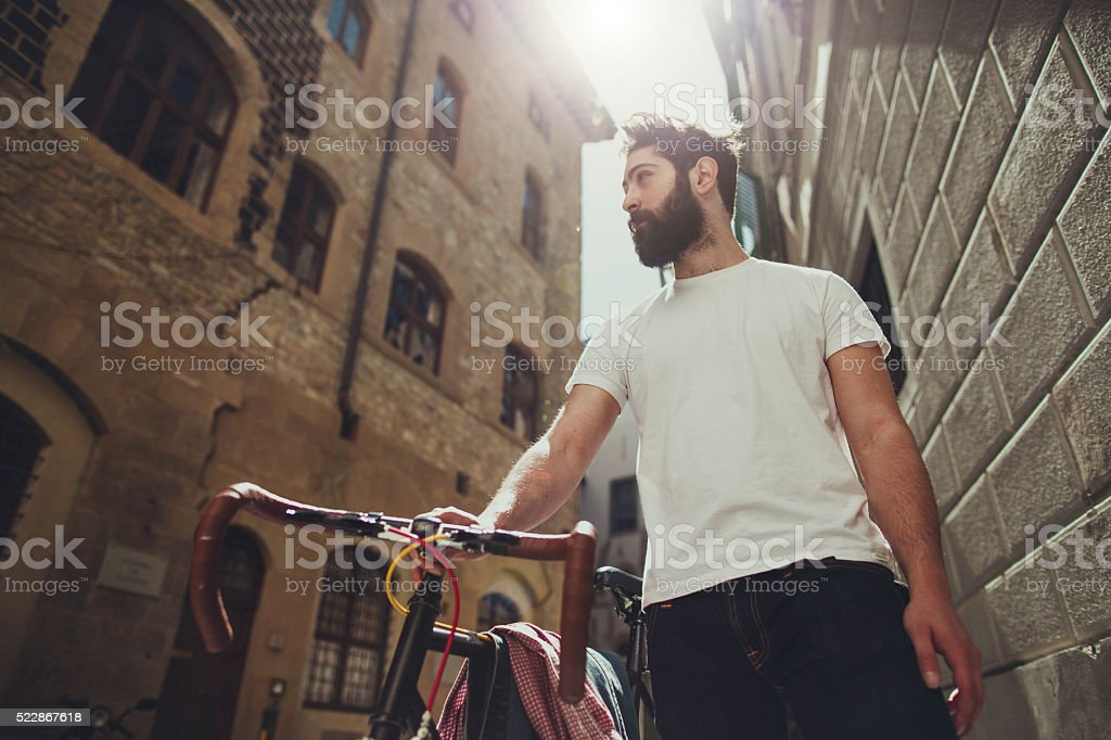 Hipster  guy walking with bicycle stock photo