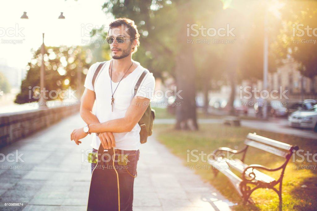 Hipster holding a longboard stock photo