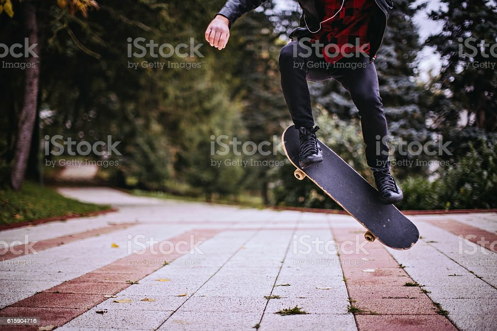 Hipster jumping with a skateboard stock photo
