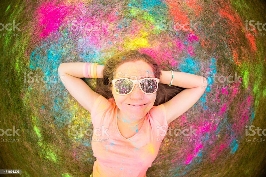 Hipster lying on grass at holi festival with colorful powder royalty-free stock photo