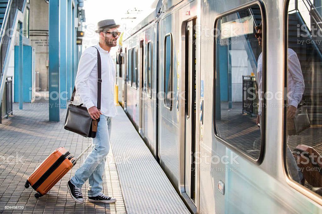 Hipster Male Boarding Train with Suitcase stock photo