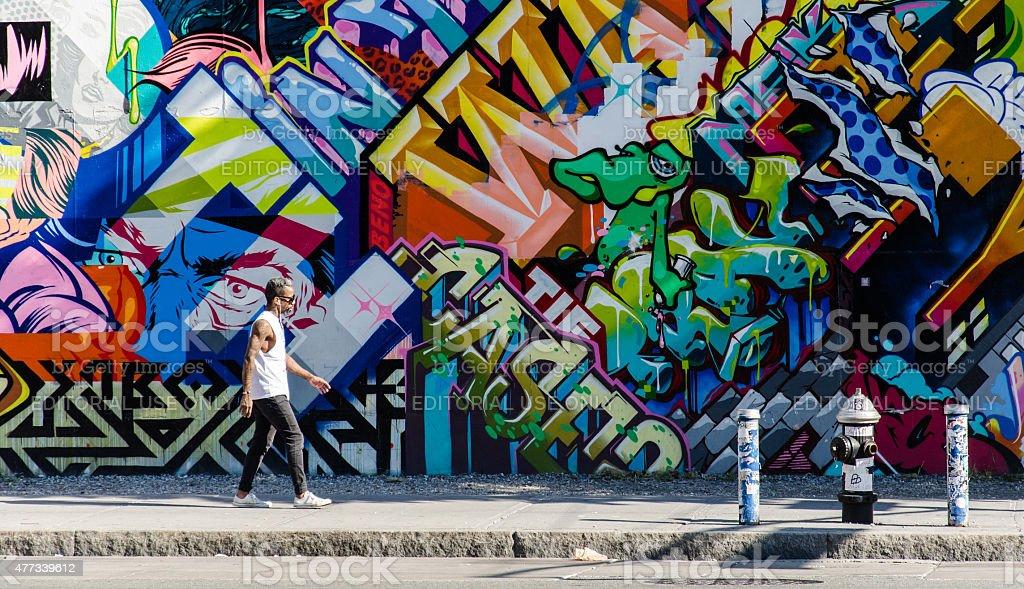 hipster hombre caminar junto a la pared de graffiti en brooklyn foto de stock libre de