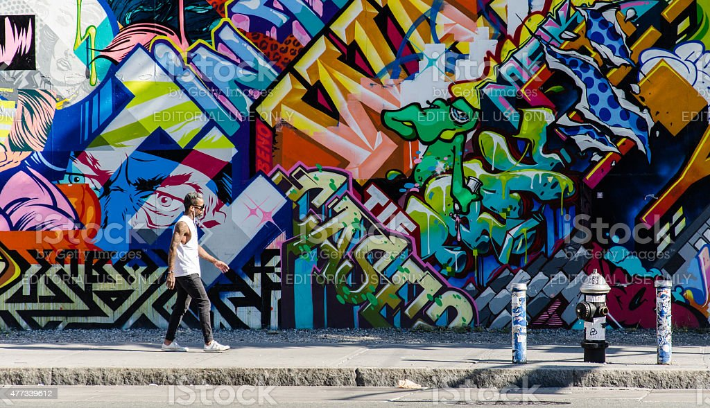 Hipster male walking next to wall of graffiti in Brooklyn stock photo