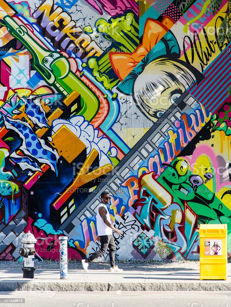 Hipster male walking next to wall of graffiti in brooklyn for Immagini di murales e graffiti