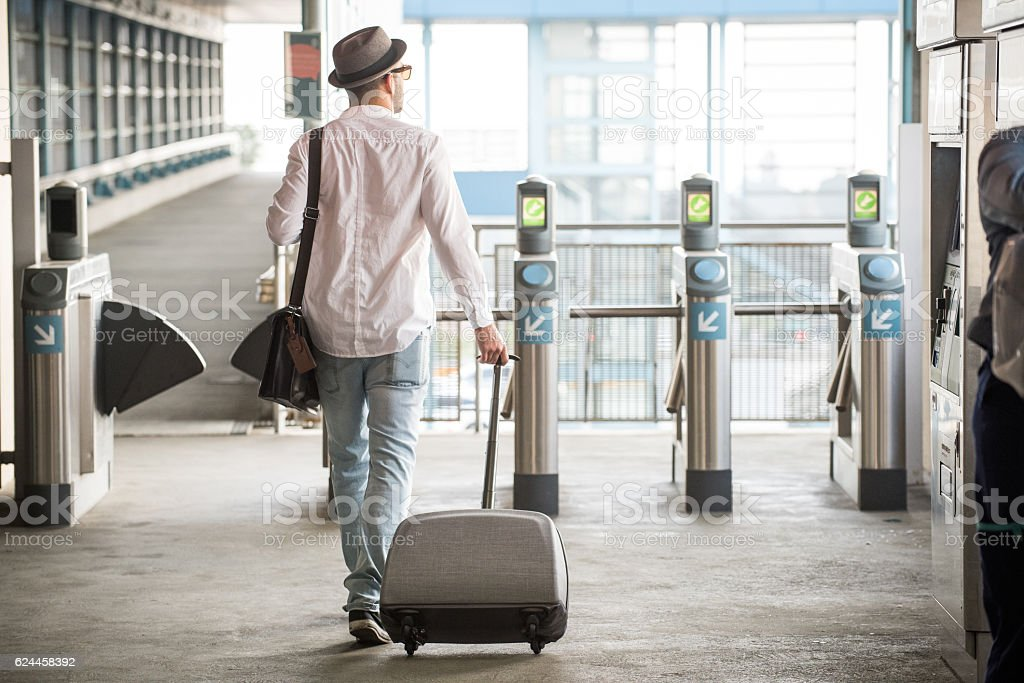 Hipster Male Walking Through Turnstile with Suitcase stock photo