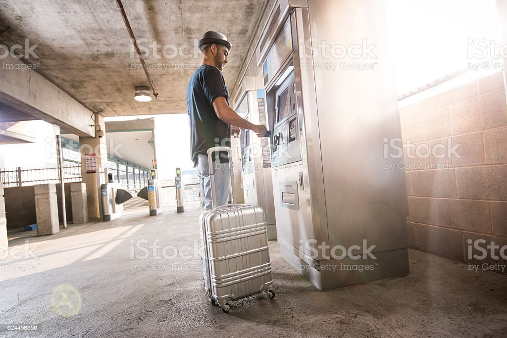 Hipster Male with Suitcase Buys a Train Ticket stock photo