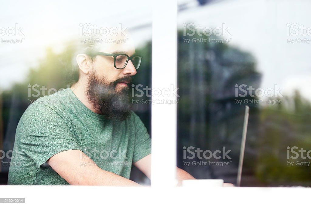 Hipster Man Behind Window Working On Laptop stock photo