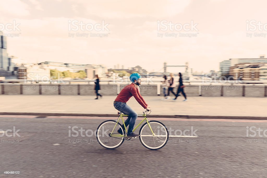 Hipster man cycling on London bridge with fixed gear bike stock photo