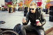 Hipster man having morning coffee and using mobile phone