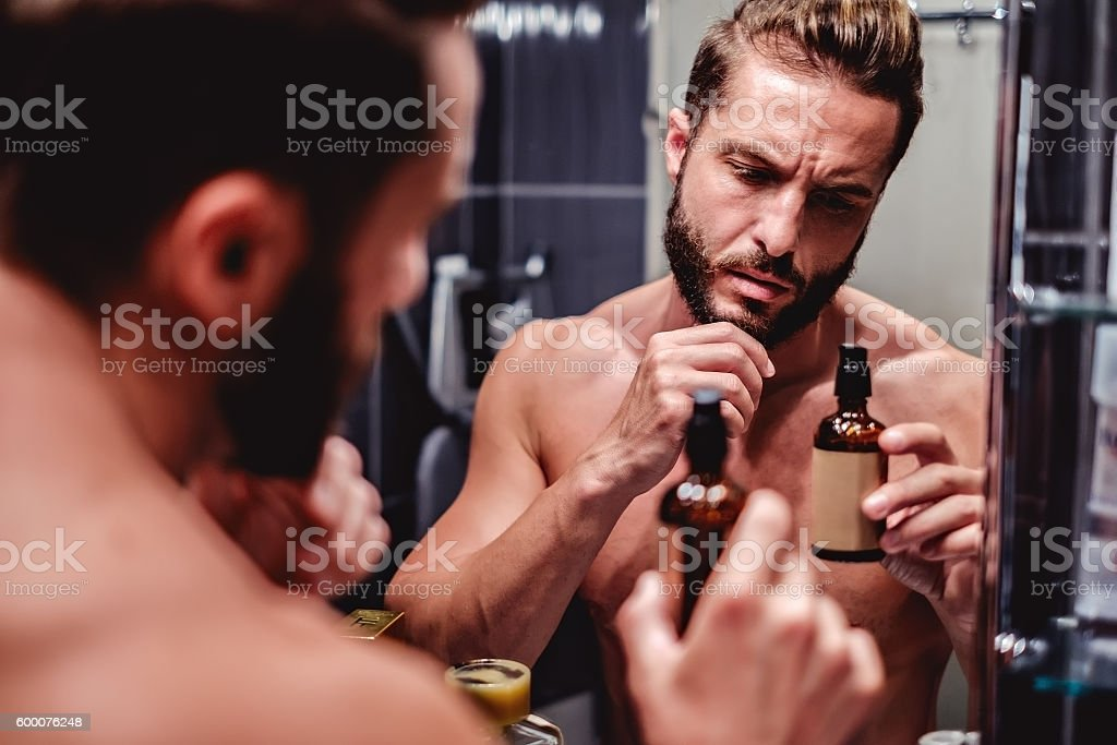 Hipster man holding bottle in the bathroom stock photo