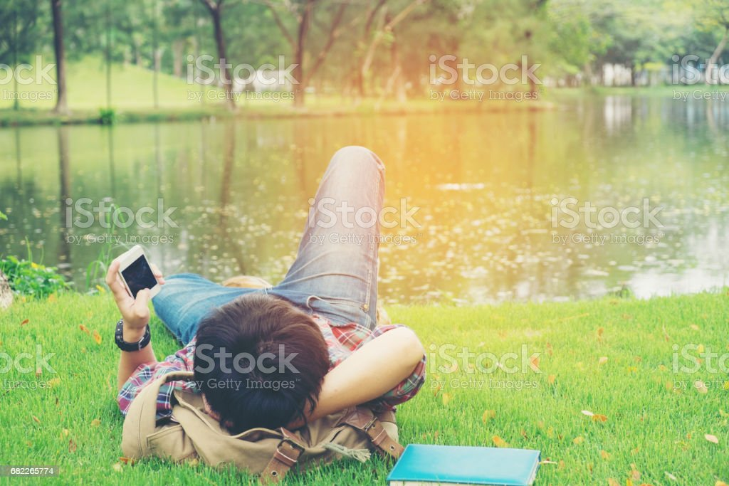 Hipster Man Relaxing on the Grass and using smart phone stock photo