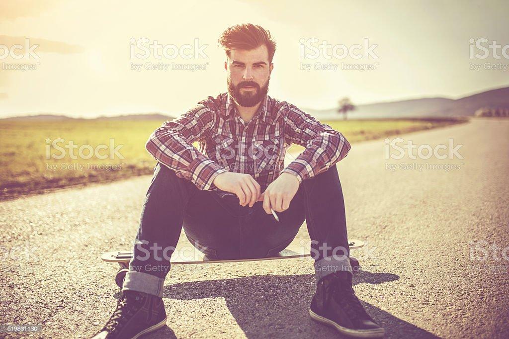 Hipster man Skateboarding stock photo