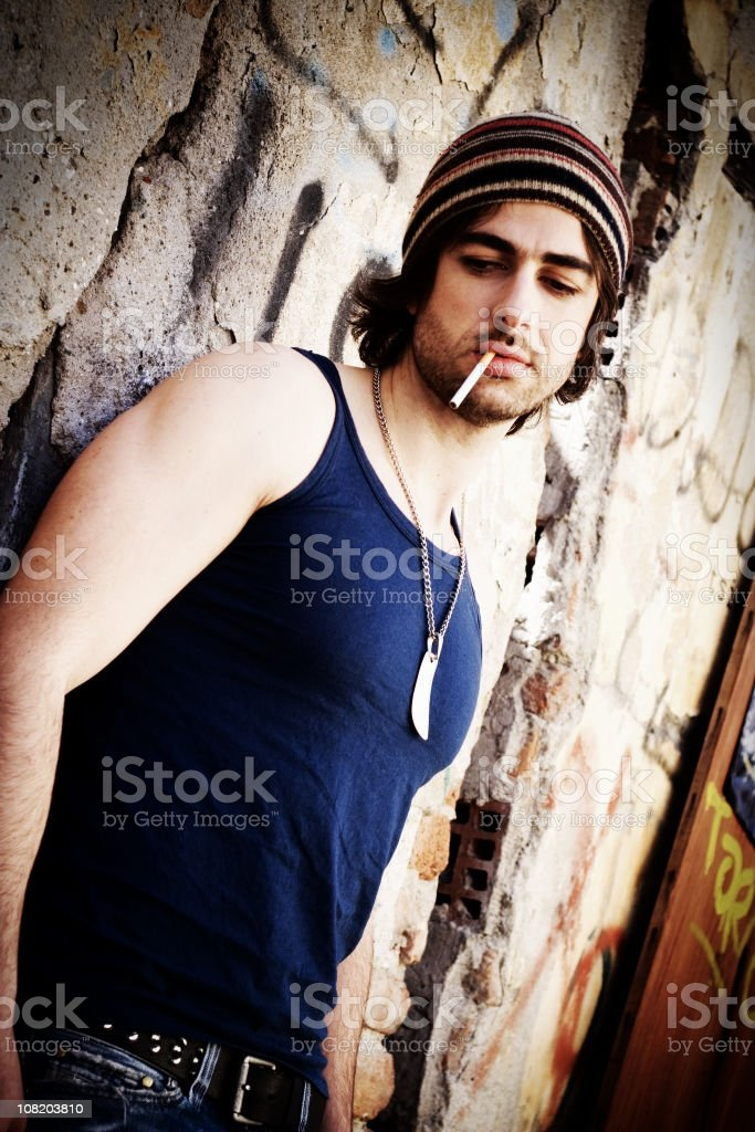 Hipster Man Smoking Cigarette Against Wall stock photo