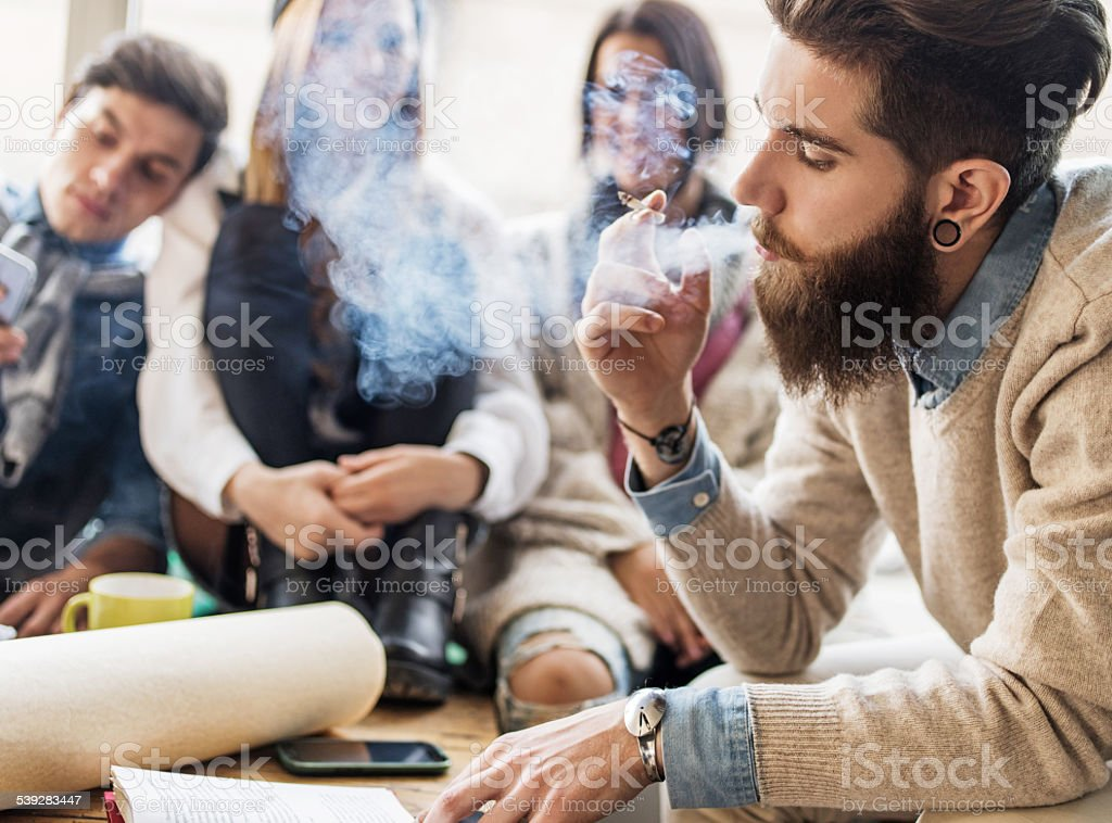 Hipster man smoking cigarette while reading a book. stock photo
