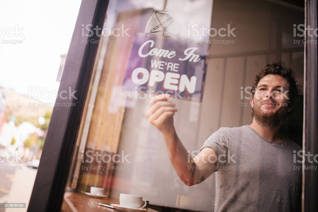A smiling and positive hipster man turning an opening sign on glass...