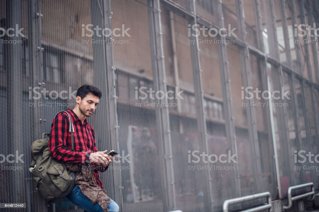 Attractive young man standing outdoors and texting on the phone