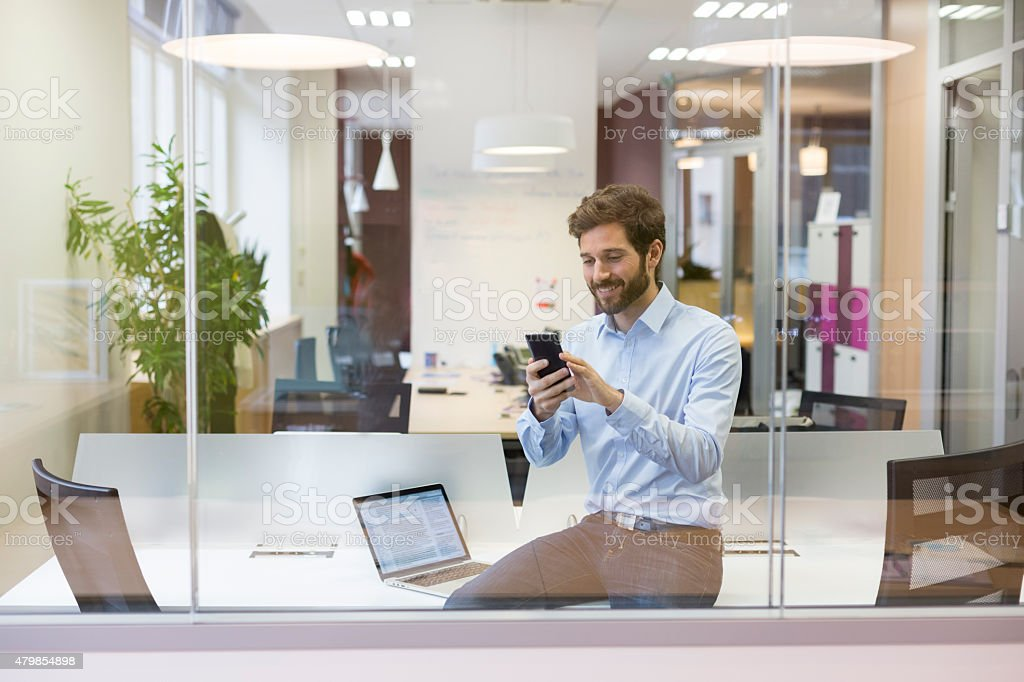Hipster man typing text on mobile phone in open space stock photo