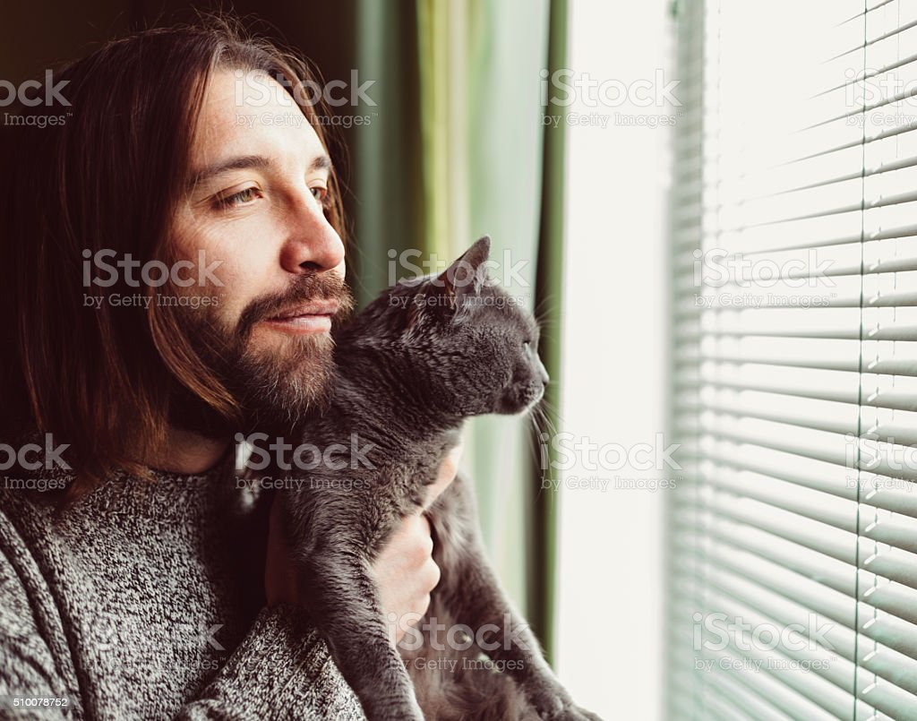 Hipster man with cat looking through the window stock photo