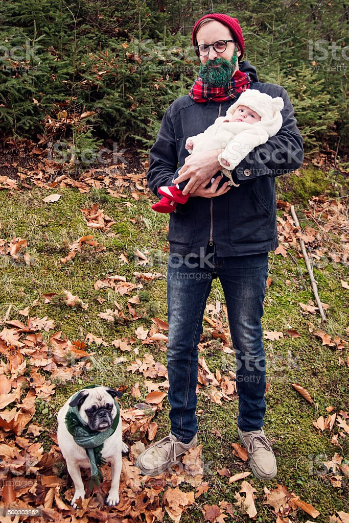 Hipster man with glitter beard holding baby with pug outdoors. stock photo