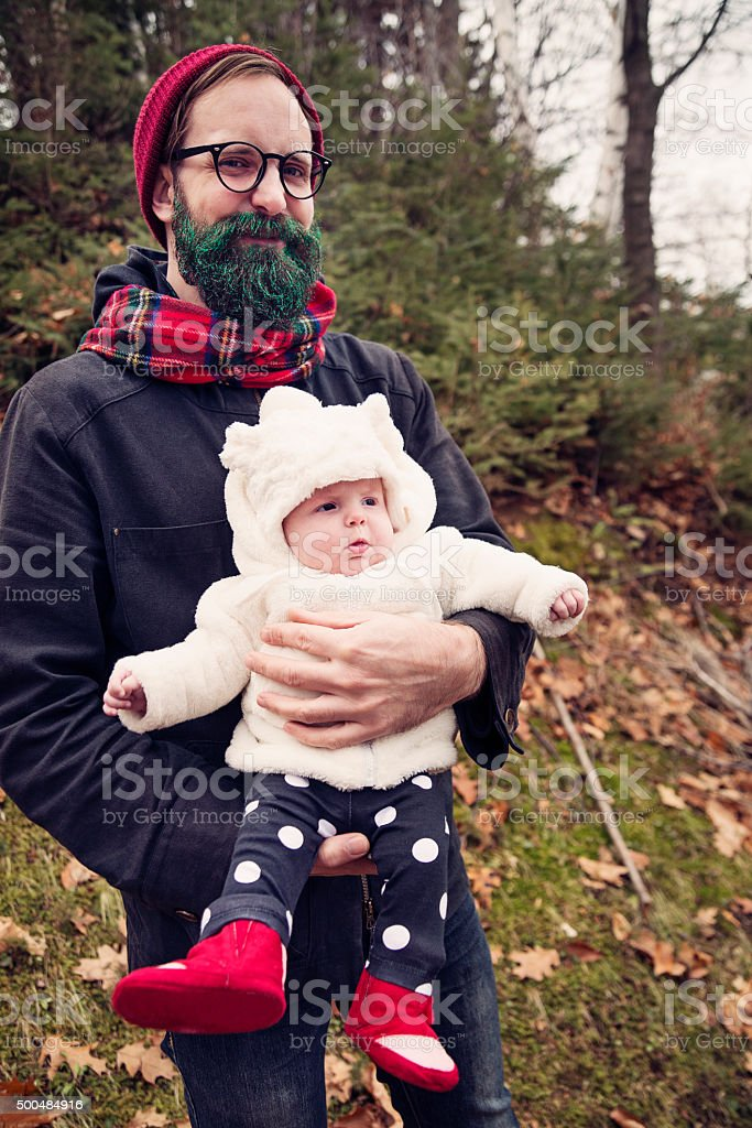 Hipster man with green glitter beard holding baby outdoors. stock photo
