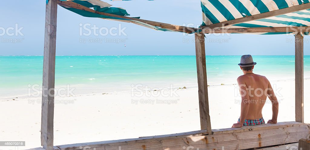 Hipster man with hat on tropical sandy beach. stock photo
