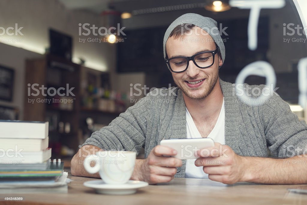 Hipster man with mobile phone at cafe stock photo