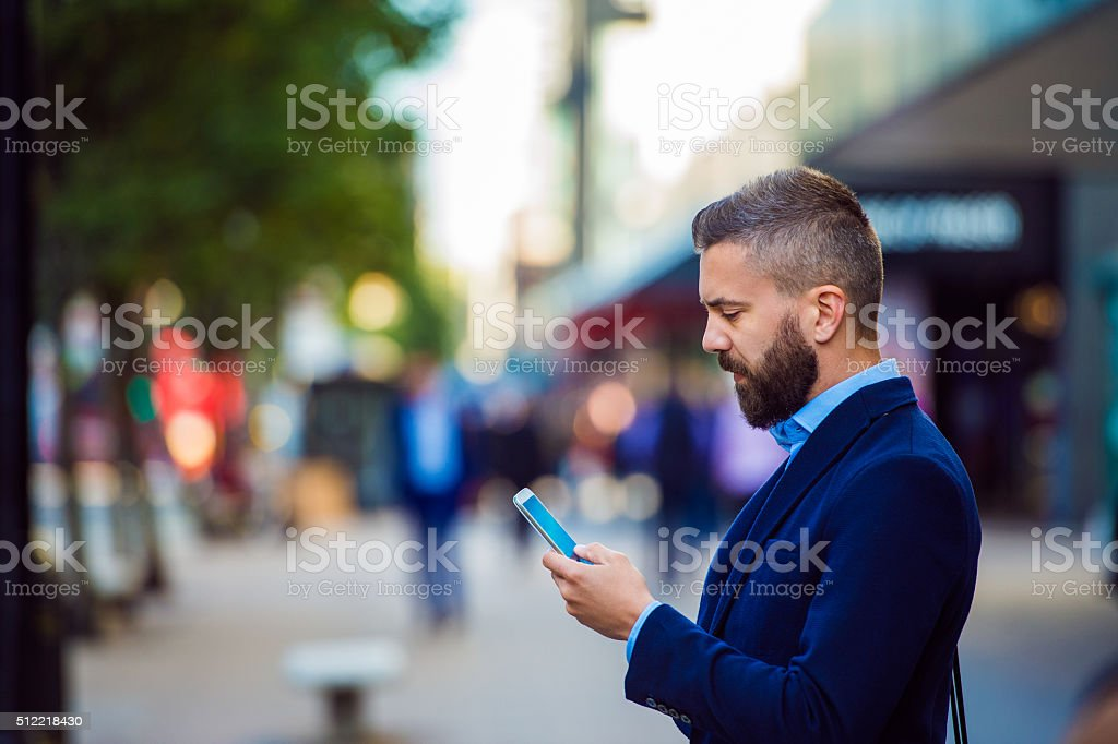 Hipster manager holding smartphone, texting outside in the stree stock photo