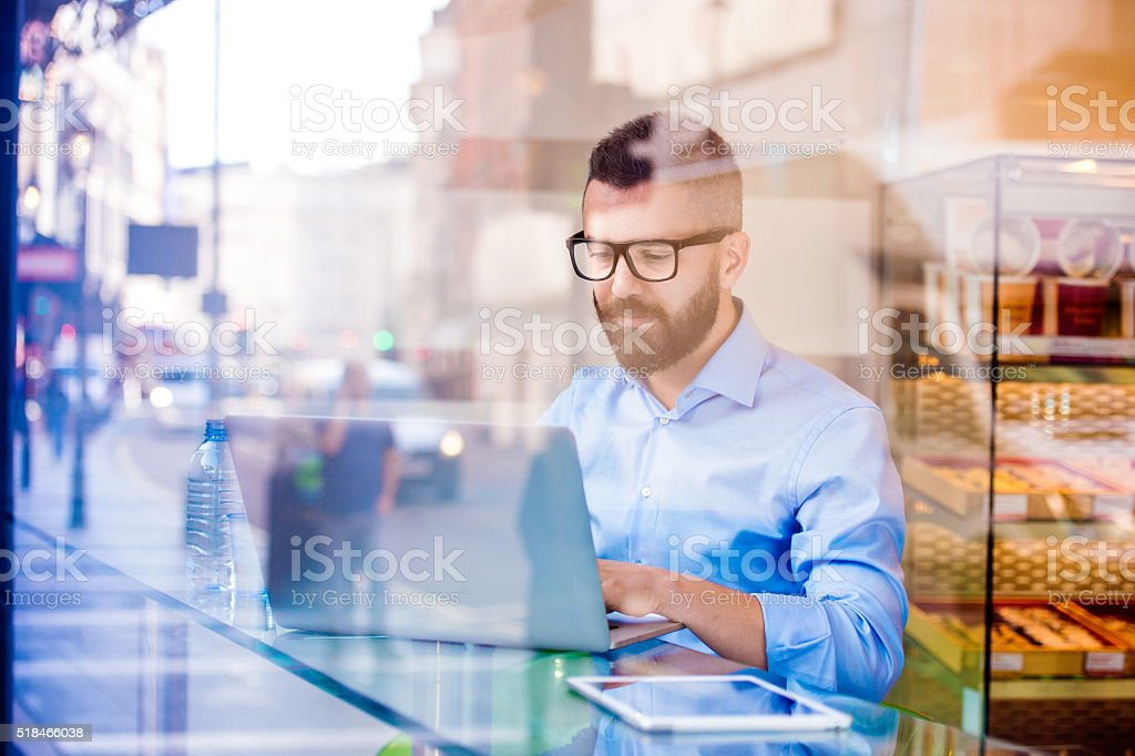 Hipster manager in cafe, working on laptop by window stock photo