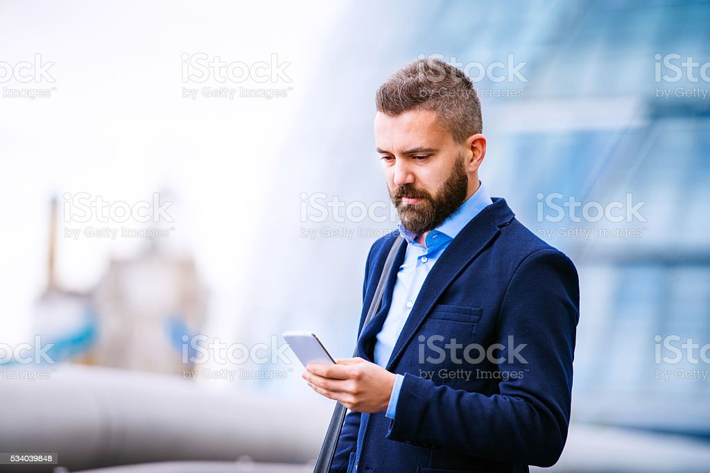 Hipster manager with smart phone, London City Hall stock photo