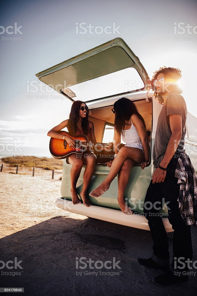 Hipster Multi-Ethnic Group Play Guitar at Beach stock photo