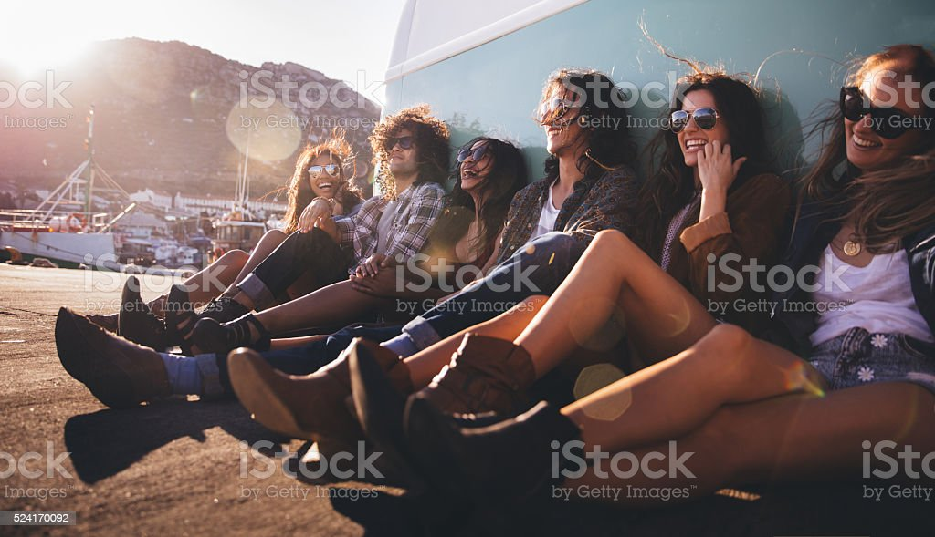 Hipster multi-ethnical friends resting out of their van at sunse stock photo