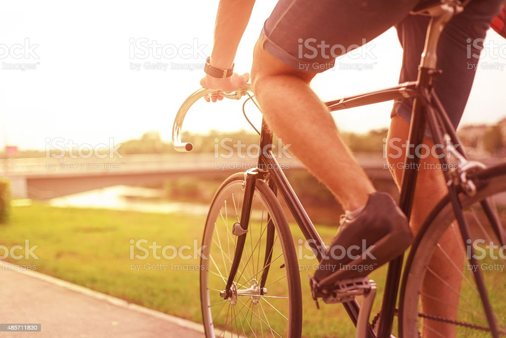 Hipster on bike in the city at sunset stock photo