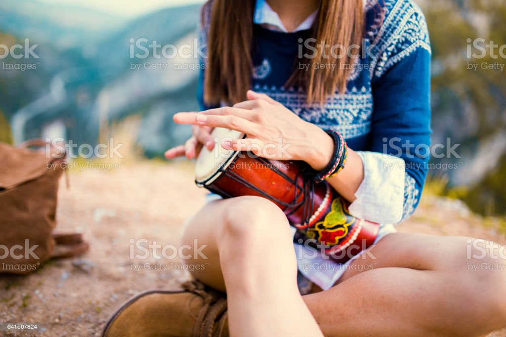 Hipster playing djembe stock photo