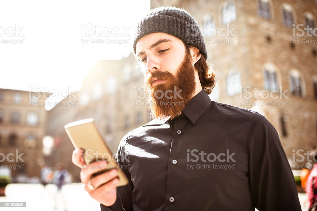 Hipster portrait in Florence look at the phone stock photo