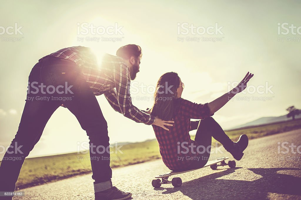 Hipster pushing girl on a longboard stock photo
