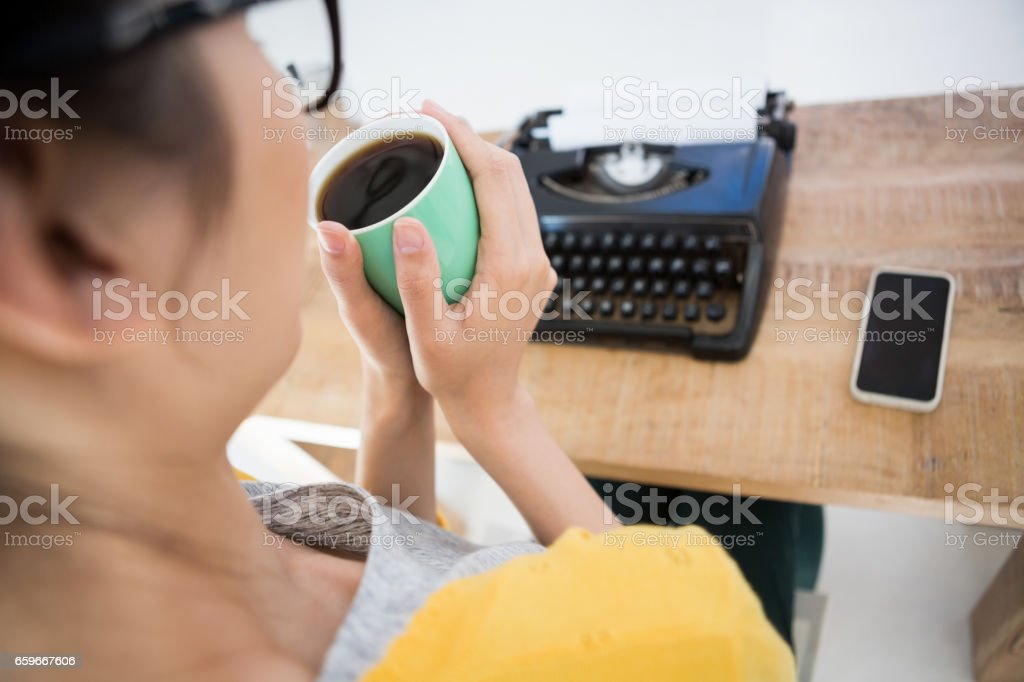 Hipster sitting in front of a type writer royalty-free stock photo