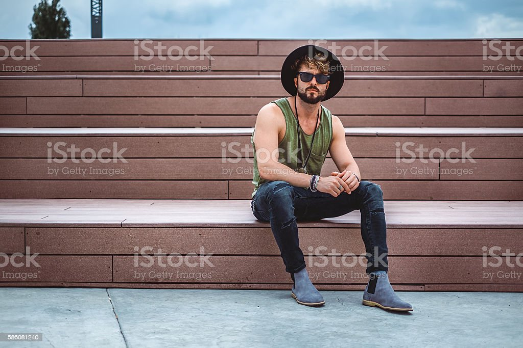 Hipster sitting on the stairs stock photo