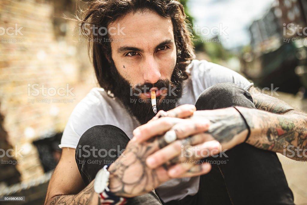 Hipster smoking and thinking sitting sad stock photo