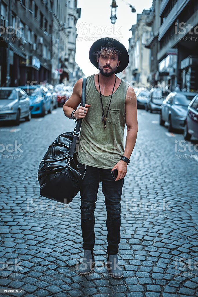 Hipster standing in the street carrying his bag stock photo