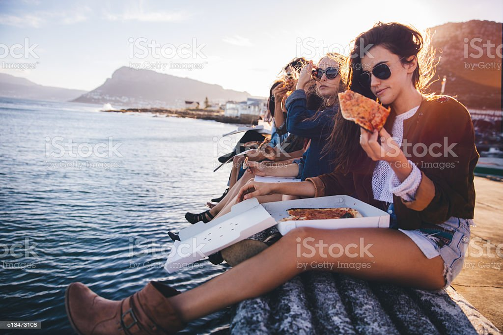 Hipster style teenager friends eating pizza on the dock stock photo