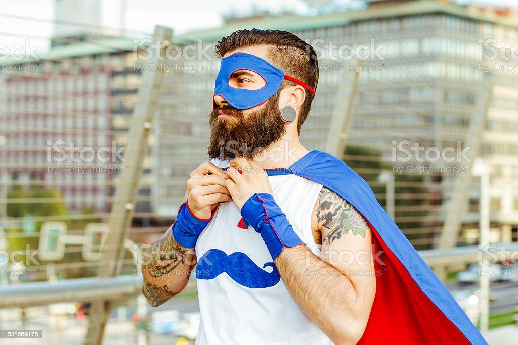 Hipster superhero adjusting his mantle stock photo