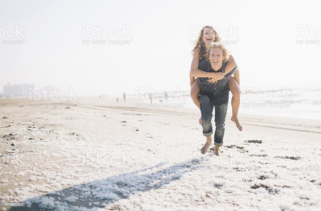 Hipster surfer boy giving his girlfriend a piggy back ride royalty-free stock photo