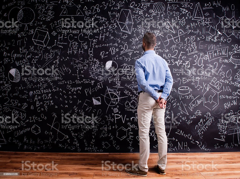 Hipster teacher against big blackboard with mathematical symbols stock photo