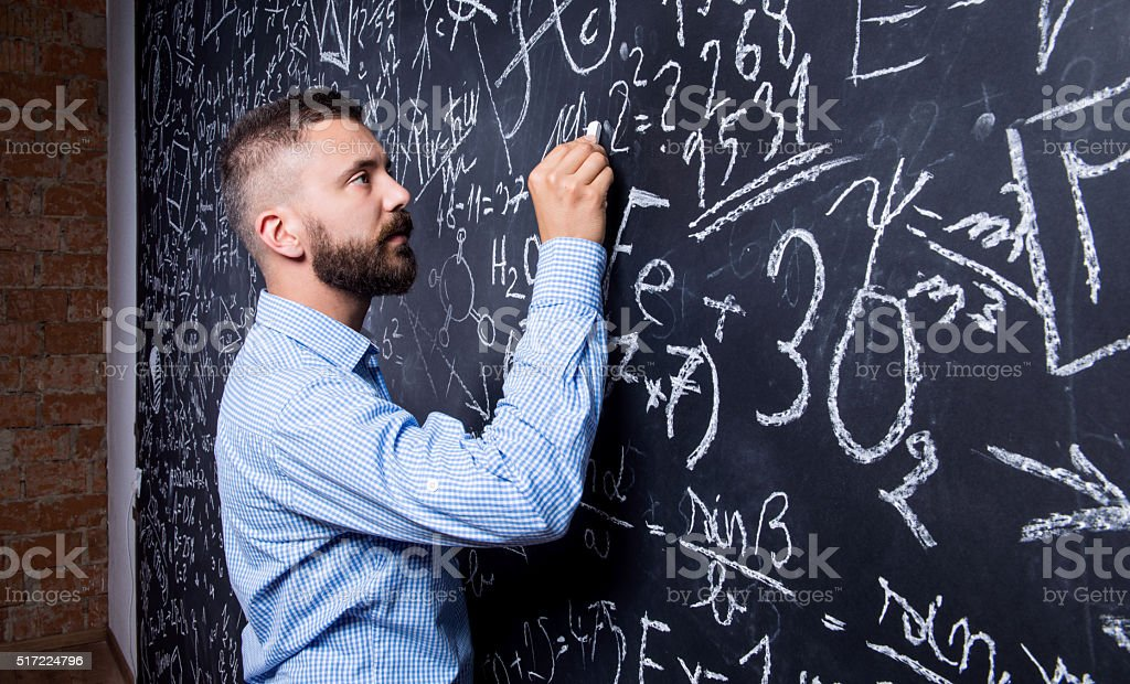 Hipster teacher writing on big blackboard with mathematical symb stock photo