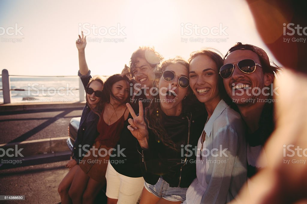 Hipster teen friends taking a selfie outdoors at the beach stock photo